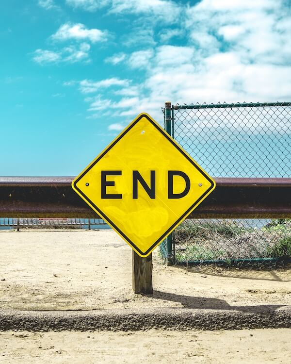 "A yellow road sign with the text ""End"" written on it"