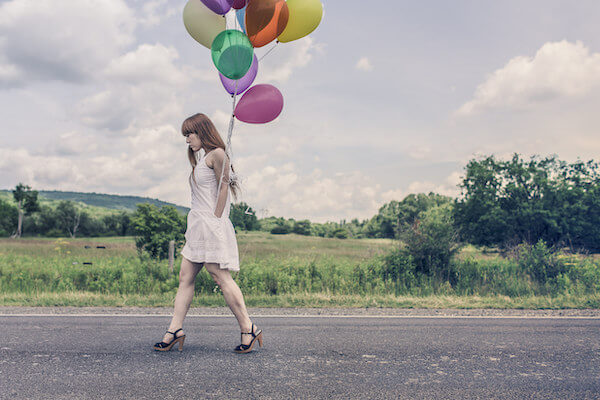 A woman walking along a road carrying a lot of colorful balloons