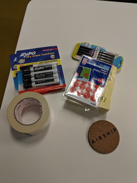 A table with masking tape, whiteboard markers, dot stickers, and Post-It notes.