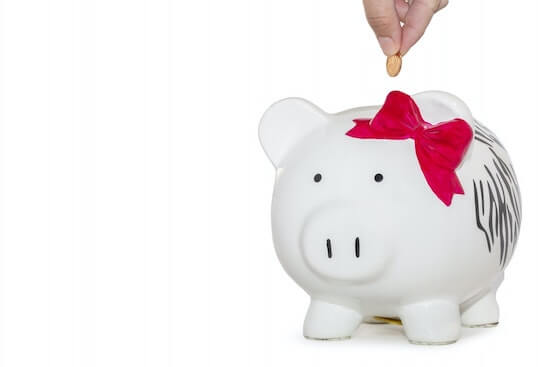 A piggy bank with a hand dropping a coin into it.